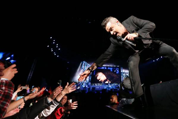 Robbie Williams greeting fans at the front of the stage.