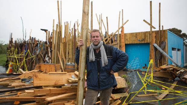 "Cafe owner Ben Meier with the recycled timber ""fence"" that has upset many Haumoana residents."