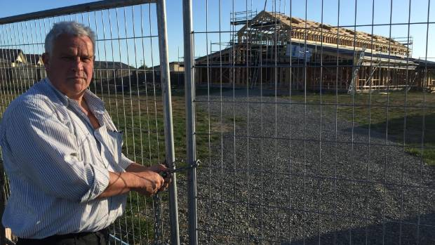 Barry Jones stands in front of his half finished house after project manager Encell Group Ltd went into liquidation.