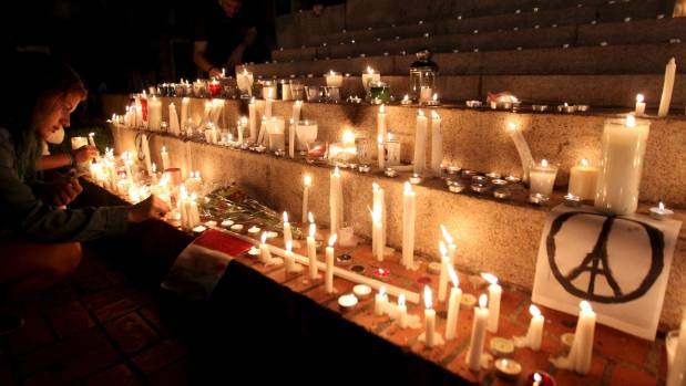 People light candles in tribute to the victims of Friday's Paris attacks, in Santo Domingo, Paris.