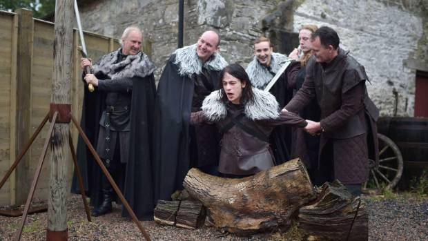 """Lead Game of Thrones tour instructor William Kells prepares to """"behead"""" a tourist as part of the Winterfell experience ..."""