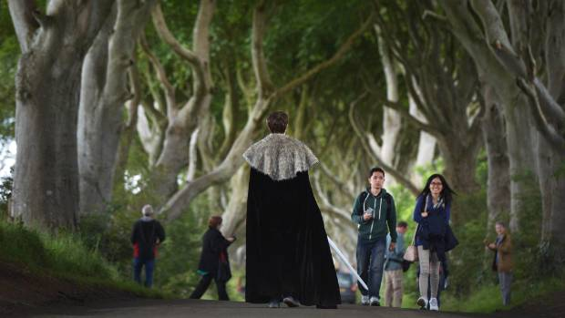 Game of Thrones tourists take photographs of one another as they visit a tree-lined road known locally as The Dark Hedges.