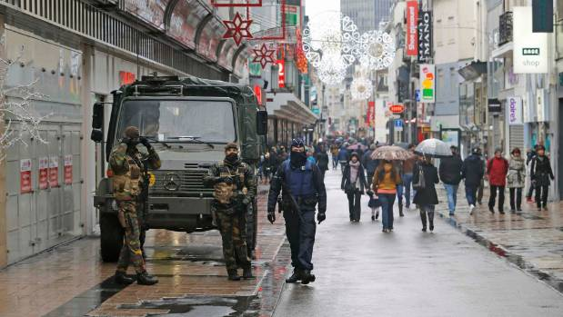 Belgian soldiers and a police officer patrol a shopping street in central Brussels.