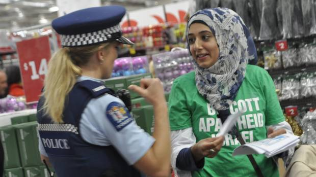 Dr Aisha Sarwar of the Palestine Human Rights Campaign talks to police during the protest at The Warehouse in Hamilton ...