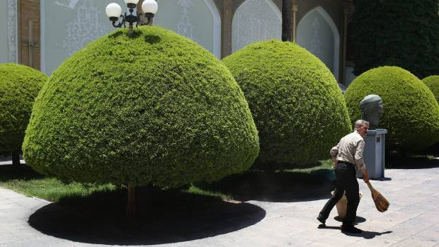 A groundskeeper sweeps in the garden of the Contemporary Art Museum in Isfahan