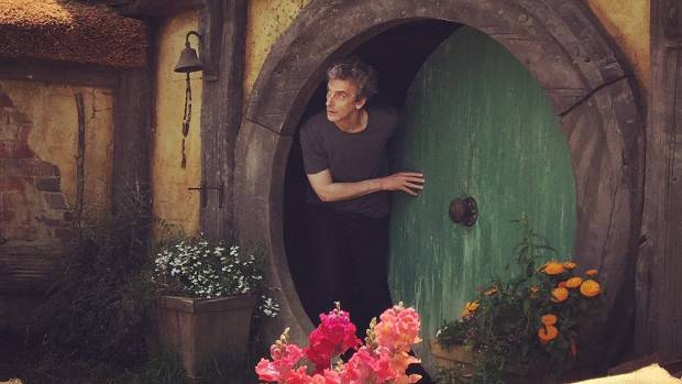 Doctor Who actor Peter Capaldi peers out of the front door of a hobbit hole at Hobbiton.