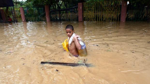 A boy carries supplies through waist-high floodwater in the Philippines, caused by Tropical Storm Ketsana.