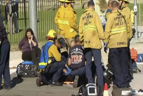 Rescue crews tend to the injured in the intersection outside the Inland Regional Center in San Bernardino, California.