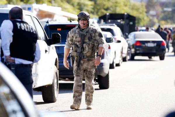 Police officers secure the area after at least one person opened fire at a social services agency in San Bernardino, ...