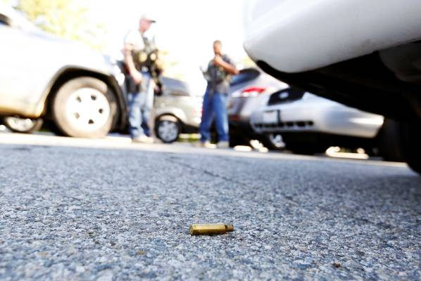 A spent cartrdige lies on the ground as police officers secure the area after at least one person opened fire at a ...