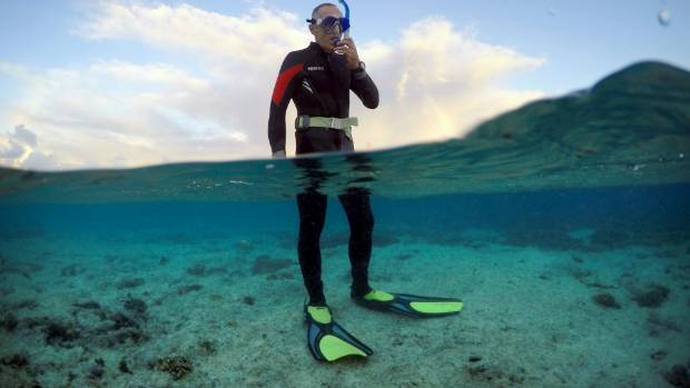 Peter Gash prepares to snorkel during an inspection of the reef's condition.