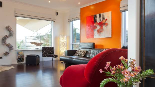 A wall painted in bright orange Resene Clockwork Orange is teamed with a rich red sofa and black furnishings in this ...