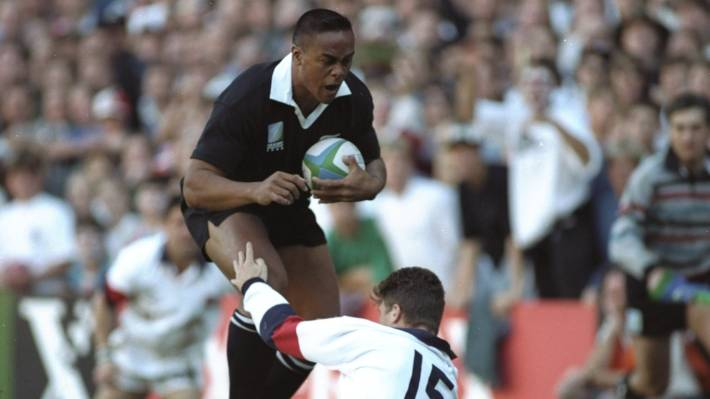 All Blacks wing Jonah Lomu charges through the tackle of England fullback Mike Catt for one of his four ties in the 1995 Rugby World Cup semifinal in Cape Town.