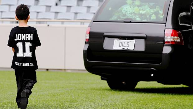 Jonah Lomu's son Dhyreille walks behind the hearse containing his father's casket as it leaves Eden Park.