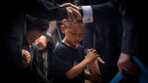 Jonah Lomu's sons Brayley and Dhyreille mourn at their father's funeral.
