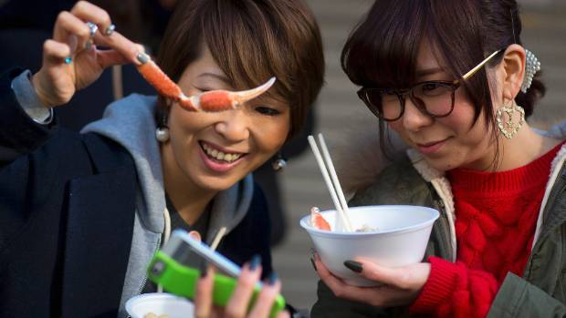 Women take pictures of themselves as they hold seafood in the outer part of the Tsukiji fish market.