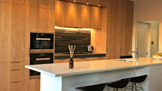 This new kitchen designed by Ingrid Geldof teams bookmatched timber veneer with black and white.