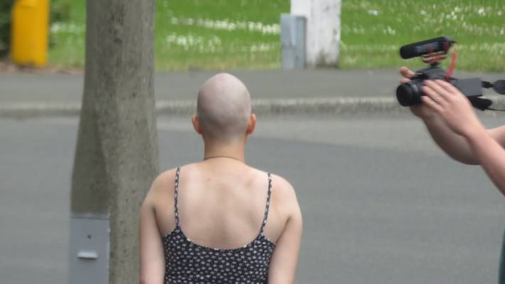 Backpackers have been paid by a mysterious benefactor to have their hair shaved off.