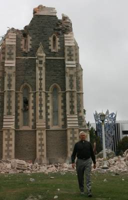 Dean Peter Beck beside his damaged cathedral shortly after the quake.