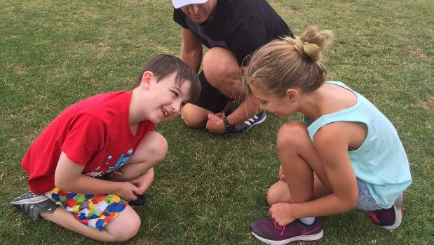 Zac Fogarty (8) and Grayce Gill (10) demonstrate the kneeling squat for quad stretching and ankle and hip mobility