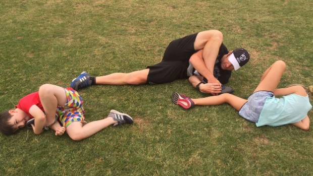 """The tough one: Zac Fogarty (8) and Grayce Gill (10) exercise glutes, hips and lower back with the """"foot in mouth"""" stretch."""