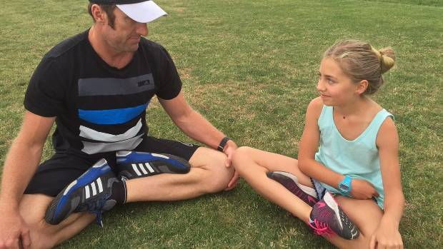 """Nic Gill coaches Grayce Gill (10) in the """"super-crossed legs"""" position for improved ankle and hip mobility."""