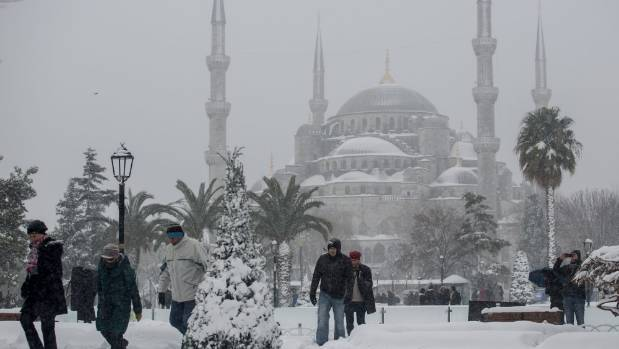 People walk through snow on the grounds of the Blue Mosque after a heavy snow storm on December 31, in Istanbul, Turkey.