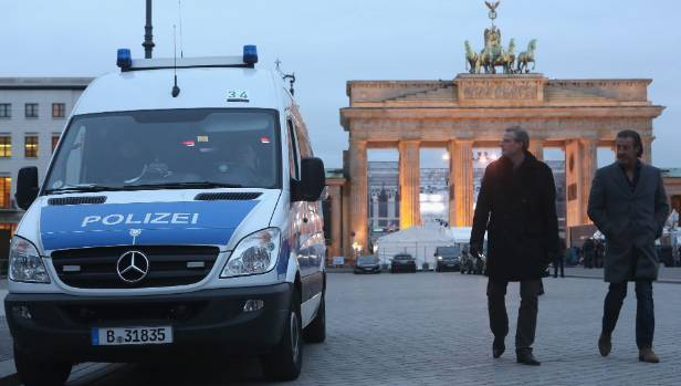 A police van sits outside the Brandenburg Gate prior to a public New Year's Eve party in Berlin, Germany.