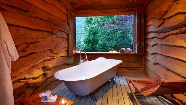Surrounded by bush, the bathtub in the bush lodge has views out across the Kahurangi National Park.