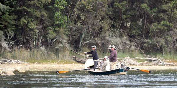 Te Anau fishing guide Steve Saunders, with American visitors Jack and Wendy Reilly, of Idaho, dry fly fishing in ...