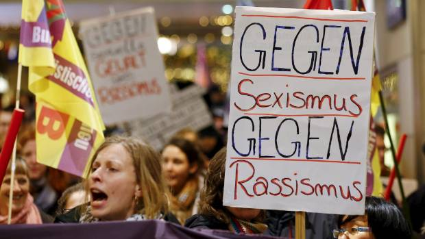 "Women shout slogans and hold up a placard that reads ""Against Sexism - Against Racism"" as they march through Cologne."