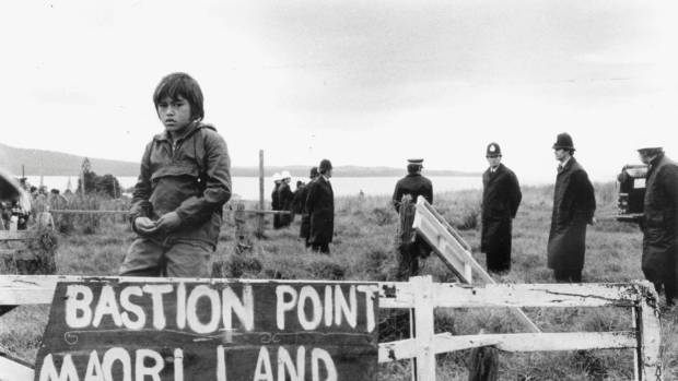 A boy sits on the fence of the occupied Bastion Point settlement, watched by police.