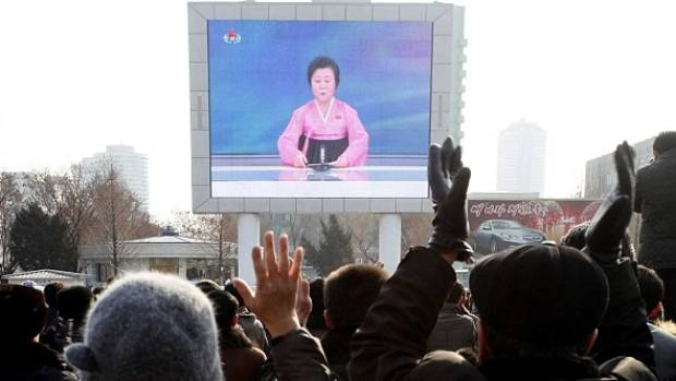 "North Koreans watch a news broadcast on a video screen outside Pyongyang Railway Station announcing the ""successful"" ..."