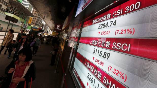 People walk past a panel displaying China stock market indexes, which have tumbled in recent days.
