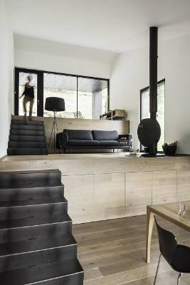 Black and light wood finishes make up the monochromatic palette on the interior - the stairs are a visual link with the ...