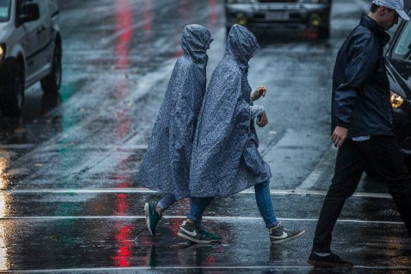 Pedestrians in Central Auckland shelter from the rain.