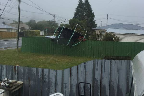 Photo of a trampoline being blown over a fence in Wainuiomata.