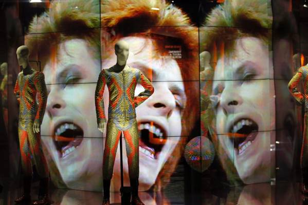 Two suits designed by Freddie Burretti (1972) for the Ziggy Stardust tour are displayed in front of a video showing pop ...