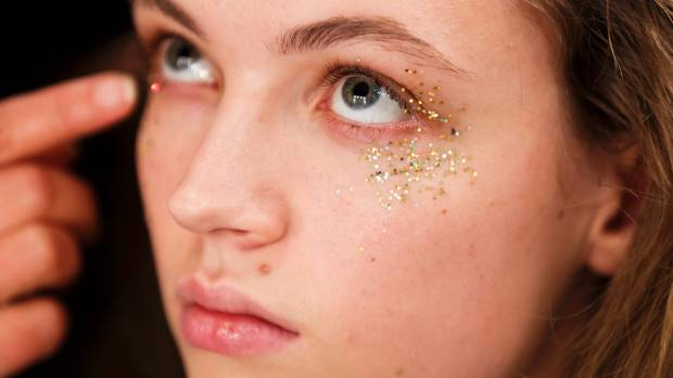A model gets glittered up backstage ahead of the Burberry show.