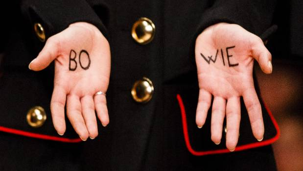 "A model with ""Bowie"" written on her hands walks the runway at the Burberry show."