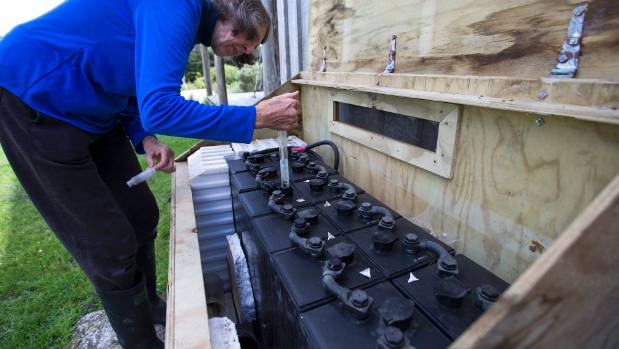 Liz Brook maintains her power house, the batteries which store her solar-sourced electricity.