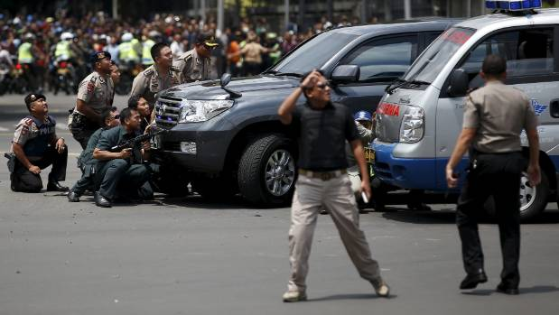 Police officers react near the site of a blast in Jakarta, Indonesia in January.