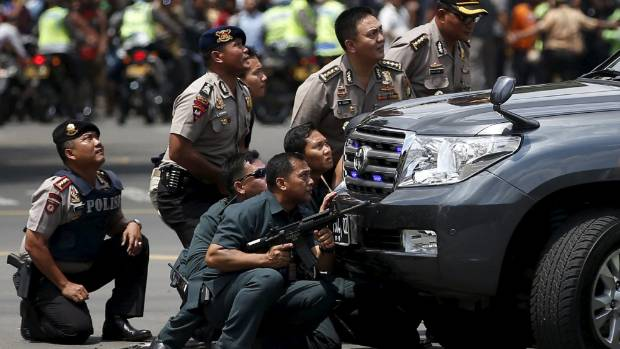 Jakarta police officers react near the site of the blasts.