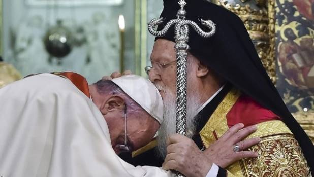 Ecumenical Patriarch Bartholomew I, right, kisses Pope Francis' head.