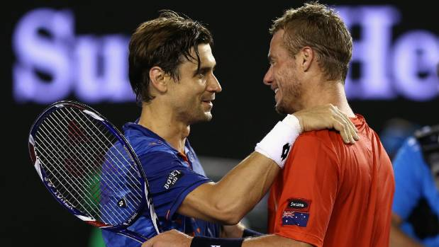 David Ferrer of Spain (left) embraces Lleyton Hewitt at the net following their second round match at the Australian ...