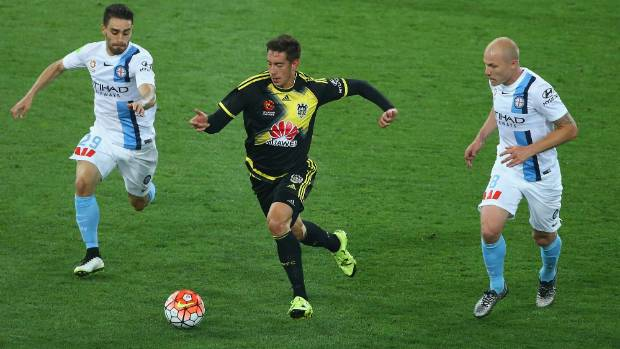Wellington Phoenix midfielder Alex Rodriguez is chased by Anthony Caceres and Aaron Mooy of Melbourne City during City's ...