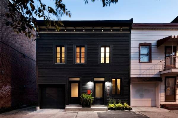 The all-black painted exterior of this renovated house, designed by Architecture Open Form, creates a touch of drama, ...
