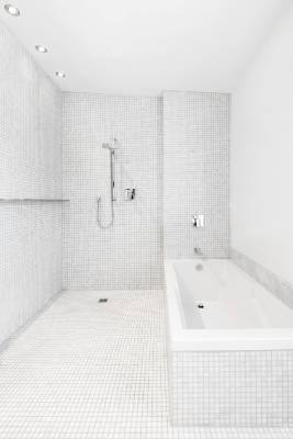 There is enough space in the white-tiled bathroom for a bath and separate wet-area shower.