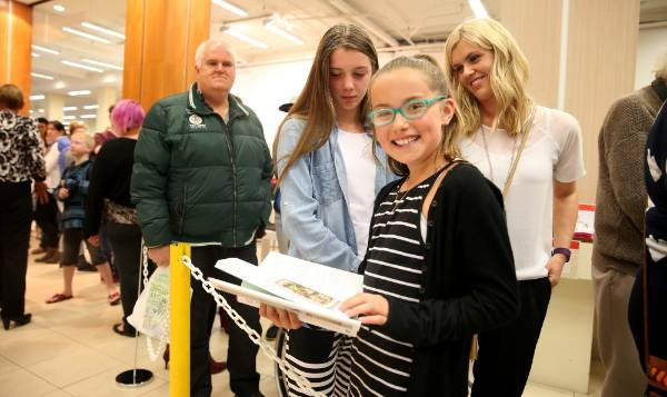 Amelia, 14, Paige, 11, and Megan McKenzie, all of Invercargill, read Nigella Lawson's book as they wait to have it signed.
