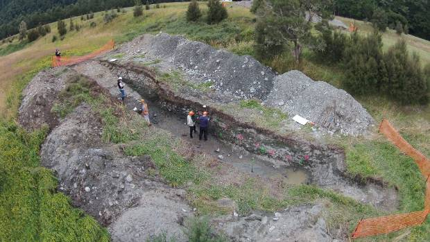 GNS Science earthquake geologists studying layers in the trench across the Alpine Fault at Springs Junction.
